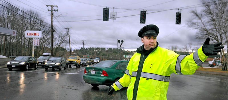 Augusta Police officer Paul Doody directs traffic at an intersection on Western Avenue Thursday following widespread power outages from high winds. Central Maine Power Co. reported about 400 customers in Somerset, Waldo, Lincoln and Sagadahoc counties remained without power at 6:55 p.m. Friday.