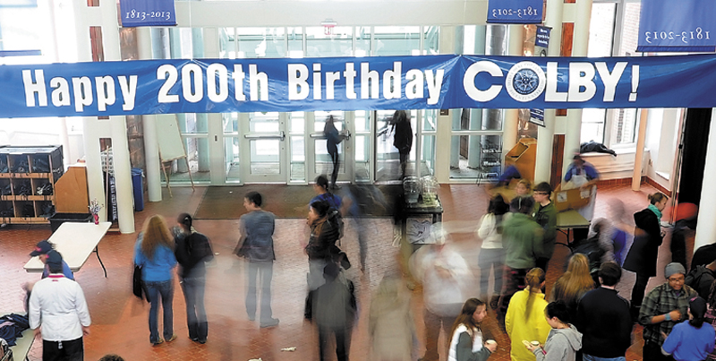 """Students and faculty walk under a banner to celebrate Colby College's 200th birthday at Cotter Union on Wednesday. The celebration featured a multi-media presentation highlighting the past 200 years and a presentation delivered by Colby College President, William """"Bro"""" Adams at the Strider Theatre."""