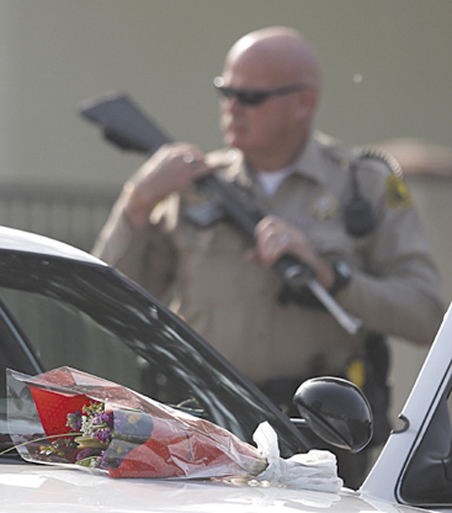 "Flowers placed on a police vehicle near the area where a shooting took place in Riverside, Calif, Thursday. Thousands of police officers are searching for one of their own: a former Los Angeles officer, Christopher Dorner, who is angry over his firing and is sought in a deadly shooting rampage after warning he would wage ""warfare"" on those who wronged him, authorities said."