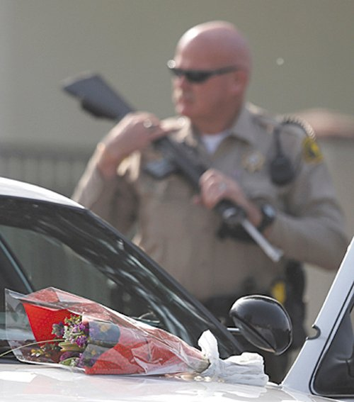 Flowers placed on a police vehicle near the area where a shooting took place in Riverside, Calif, Thursday. Thousands of police officers are searching for one of their own: a former Los Angeles officer, Christopher Dorner, who is angry over his firing and is sought in a deadly shooting rampage after warning he would wage