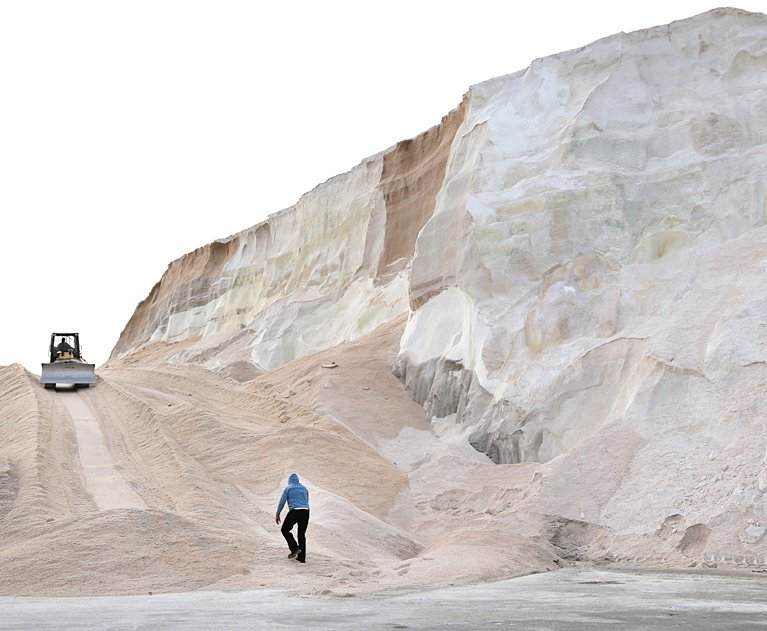 A worker walks up towards a plow smoothing a large salt pile at Eastern Salt Company in Chelsea, Mass., Thursday, in preparation for a major winter storm headed toward the U.S. Northeast. The National Weather Service calls for up to 2 feet of snow expected for a Boston-area region that has seen mostly bare ground this winter.