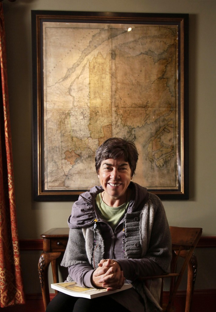 Conservationist Roxanne Quimby poses in front of a 180-year-old map of Maine at her home in Portland. Two studies commissioned by her foundation suggest communities near national parks outpace the national average for economic development.