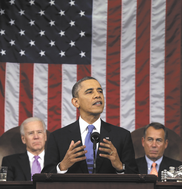President Barack Obama, flanked by Vice President Joe Biden and House Speaker John Boehner of Ohio, gestures as he gives his State of the Union address during a joint session of Congress on Capitol Hill in Washington on Tuesday. Obamas re-election and his urging of new restrictions on gun ownership have spurred a run on concealed-weapons permit applications in Maine, according to many.