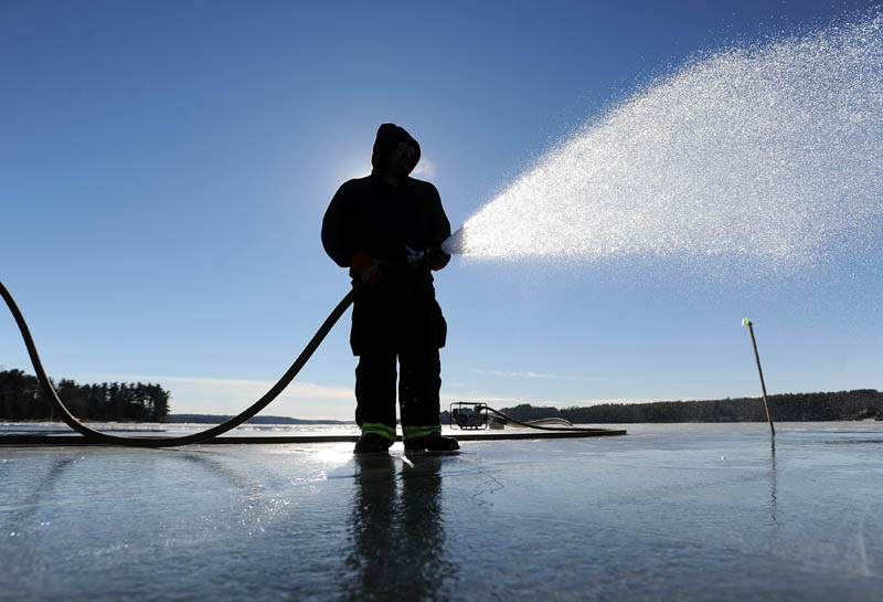 Joe Labbe, with the China Village Fire Department, sprays water on the northeast end of China Lake, off Lakeview Drive, on Thursday in preparation for Saturday's Maine Pond Hockey Classic. Volunteers are trying to get the surface ready before the impending storm settles in over the area.