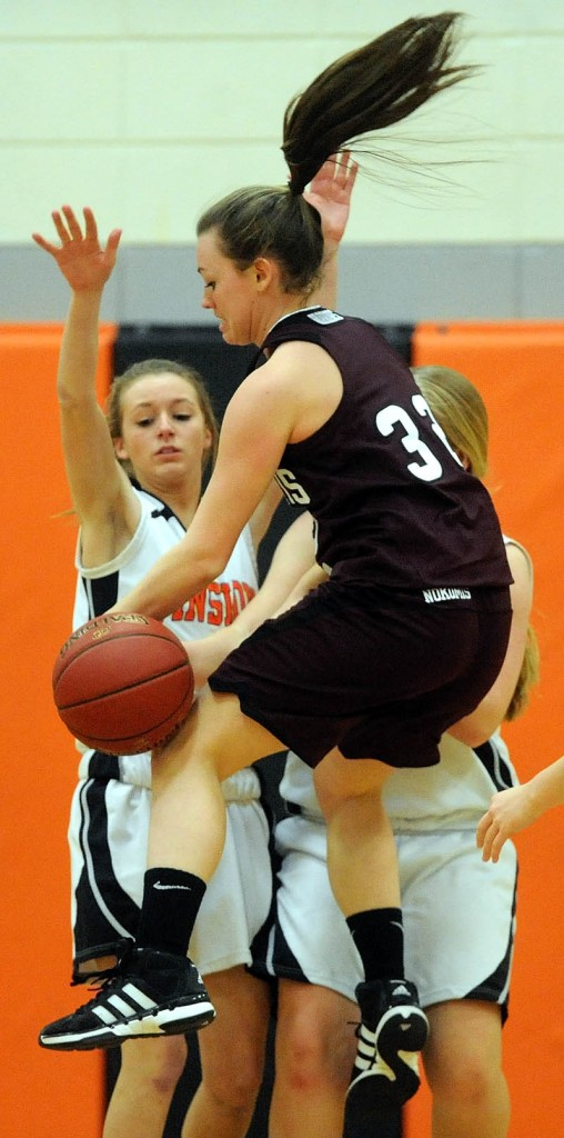 TURNOVER: Nokomis High School's Taylor Shaw (32) gets the ball stripped as Winslow High School's Erica Bertolaccini (5) and Morgan Clark (32) defend in the second quarter Tuesday in Winslow.