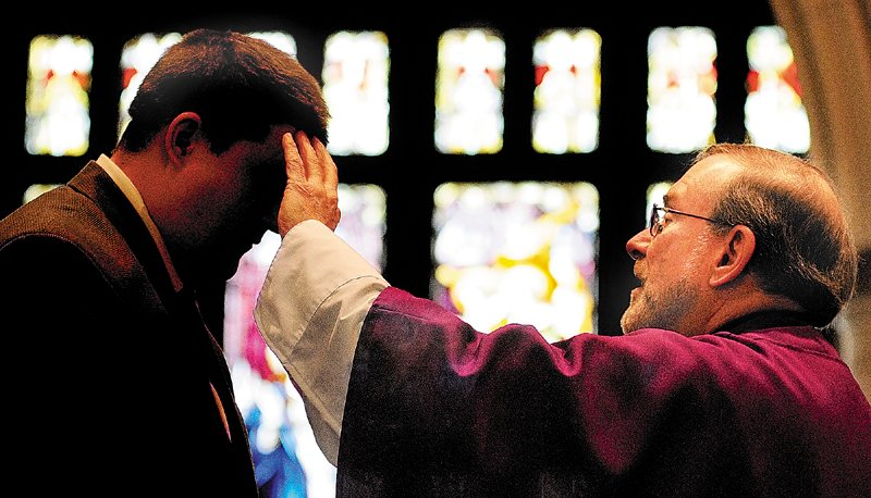 The Rev. Francis Morin places ashes on a person's forehead during an Ash Wednesday mass at St. Mary Church in Augusta.