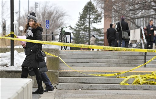 Pedestrians walk by police tape on the MIT Campus in Cambridge, Mass.,after police responded to reports of a gunman on campus on Saturday.