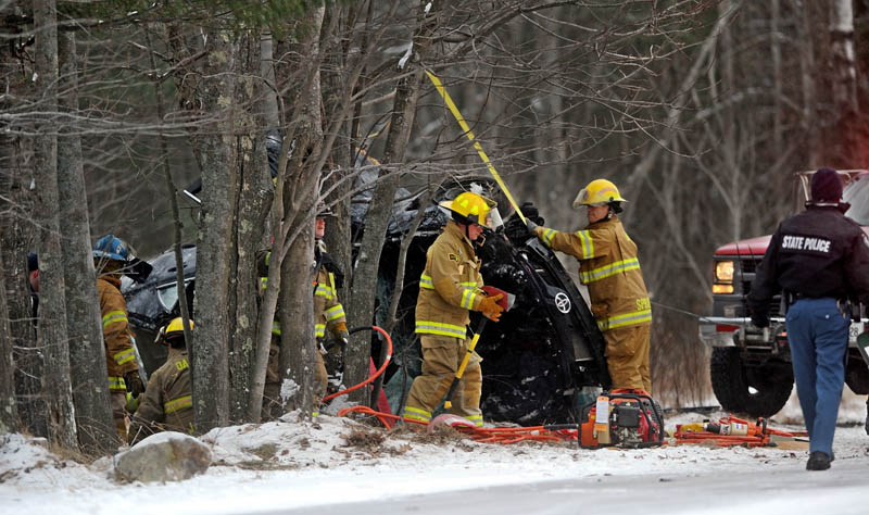 Staff photo by Michael G. Seamans Rescue workers and firefighters from Belgrade Fire Department extract a driver from a vehicle that lost control and rlled over striking trees on Route 8 near McGrath Pond Road in Belgrade Friday afternoon.