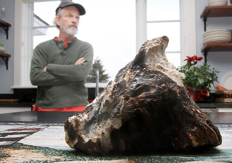 Rye, N.H. fisherman Mike Anderson says he pulled up a mammoth tooth from the depths of the ocean Tuesday, Feb. 19, 2013. Anderson said he was fishing for scallops near Rye Harbor on Tuesday. He noticed a 6-inch-long, triangular object mixed in with the scallop shells and rocks. Will Clyde, a University of New Hampshire associate professor of geology, says it may be a fossil mammoth tooth. (AP Photo/Portsmouth Herald, Ioanna Raptis)