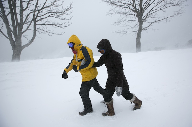 Alexandria Brahler, right, holds onto Colin Matthews, as they struggle against strong winds and blowing snow Saturday, Feb. 9, 2013 in Portland, Maine. Officials are cautioning residents to stay off the roads in Maine, where Portland set an all-time snowfall record and blowing snow continues to reduce visibility on the coast. (AP Photo/Robert F. Bukaty)