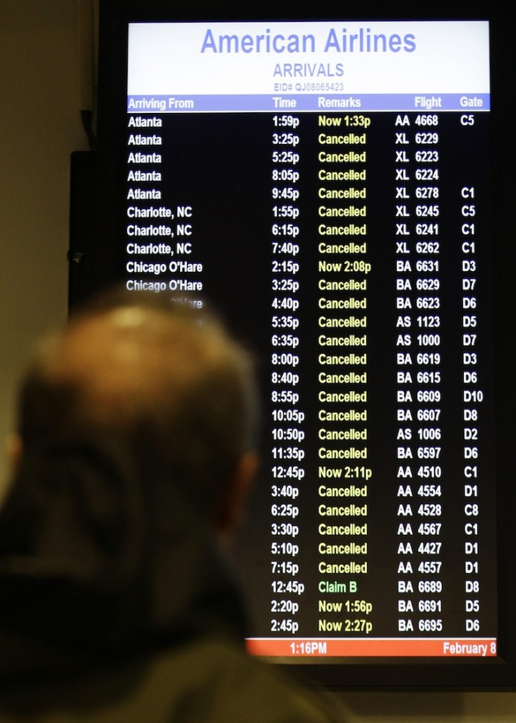 A patron checks to see if his flight is cancelled at LaGuardia Airport Friday, Feb. 8, 2013, in New York. Most airlines were giving up on flying in and out of New York, Boston and other airports in the American Northeast on Friday as a massive storm threatened to dump up to a meter of snow in some parts. (AP Photo/Frank Franklin II)