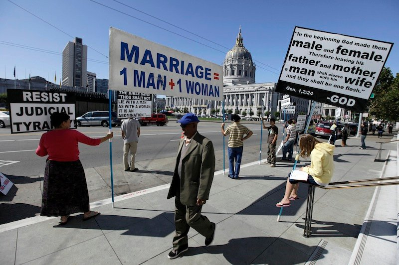 This Sept. 6, 2011 file photo shows a man walking past a group of people protesting against gay marriage outside a courtroom where the California Supreme Court was hearing arguments in San Francisco. The Obama administration on Thursday will ask the Supreme Court to overturn California's ban on gay marriage and take a skeptical view of similar bans. (AP Photo/Eric Risberg, File)