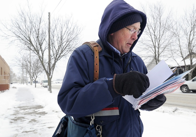 Mail carrier Bruce Nicklay walks along East Third Street in Winona, Minn., delivering letters to homes Wednesday, Feb. 6, 2013. The U.S. Postal Service will stop delivering mail on Saturdays but continue to deliver packages six days a week under a plan aimed at saving about $2 billion annually, the financially struggling agency says. (AP Photo/Winona Daily News, Andrew Link)