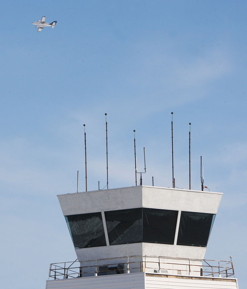 A twin engine airplane flies by the tower at St. Louis Regional Airport in Bethalto, Ill., Monday Feb. 25, 2013, before circling to land. The airport is one of 100 airports nationwide with less than 150,000 annual flights that will likely loose their air traffic control by the end of the week if a budget deal is not reached in Washington. The Federal Aviation Administration has notified the airport that it is on the list and that $600 million will be cut from the FAA's budget if sequestration cuts take effect on March 1. (AP Photo/The Telegraph, John Badman)