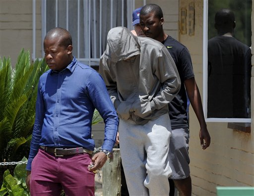 Olympic athlete Oscar Pistorius, center. leaves the Boschkop police station, east of Pretoria, South Africa, on Thursday en route to appear in court to be charged with murder.