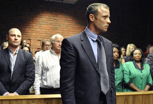 Oscar Pistorius stands following his bail hearing, as his brother Carl, left, and father Henke, second from left, look on in Pretoria, South Africa, on Tuesday.