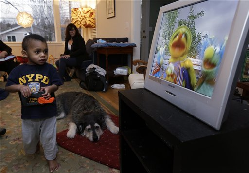 Nancy Jensen, second from left, looks on as her son Joe, 2, is given a special treat of a little TV time last week at their home in Seattle. Nancy Jensen was a participant in a new University of Washington study on the effects of television viewing on kids that will be published Monday.