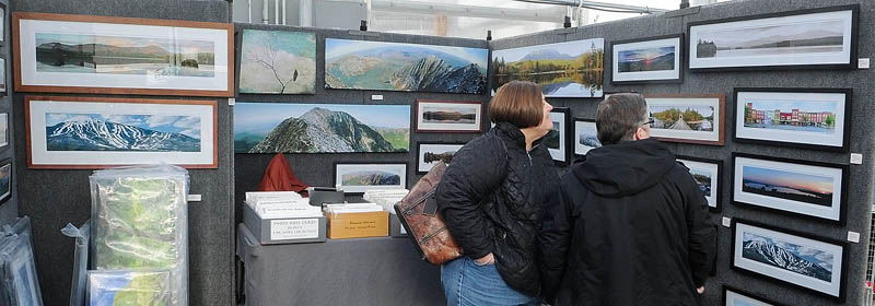 Sherry Levesque, left, and Dale Haywood, both of Winthrop, look at panoramic photos by Farmington artist Scott Perry during the Cabin Fever art show at Longfellow's Greenhouses on Saturday, in Manchester.