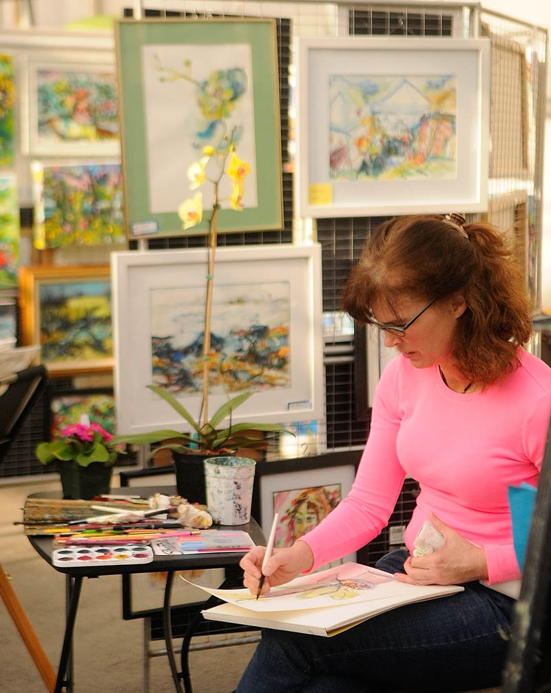 Artist Laurie Proctor-Lefebvre works in her booth while waiting for customers during the Cabin Fever art show at Longfellow's Greenhouses on Saturday, in Manchester.
