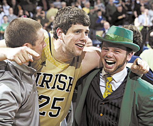MAKING GOOD: Notre Dame forward Tom Knight celebrates with Leprechaun Bryce Burton following a104-101 five overtime win against Louisville on Saturday in South Bend, Ind. Knight is a Dirigo High School graduate.