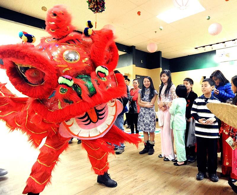 Children enjoy the dragon dance during the celebration of the Lunar New Year by the Vietnamese American Association of Maine at The Gold Room & Turf's in Portland on Saturday.