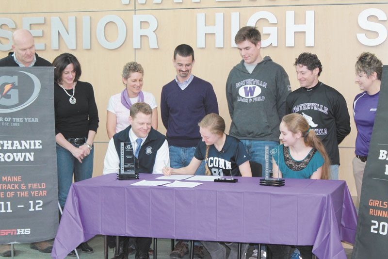 MAKING IT OFFICIAL: Waterville enior Bethanie Brown, center, signs a National Letter of Intent to compete on University of Connecticut cross country and track and field teams, Friday at Waterville Senior High School. Brown is joined at the signing by her father Ted, front left, her sister Lauren, front right, as well (back row, left to right) former Waterville athletic director Doug Frame and his wife Angela, track coaches Michelle Fowler, Rob Stanton, Matt Gilley, Ian Wilson, and Waterville athletic director Heid Bernier.
