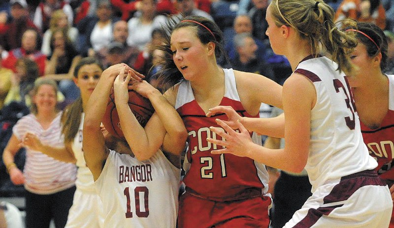 Bangor's Denae Johnson, left, battles for the ball with Cony's Alyssah Dennett, center, during the Eastern Class A championship game Friday at the Augusta Civic Center. Bangor derailed Cony's bid for a second straight regional title, winning 57-43.