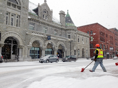 McGee construction employee Mike Abbott clears snow on Water Street in Augusta on Friday.