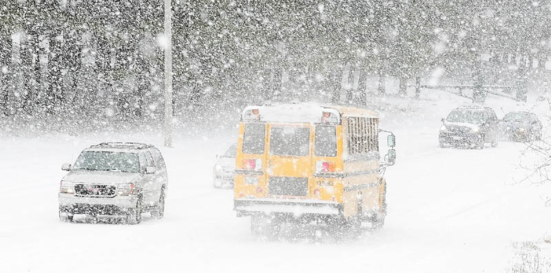 Cars drive in on Pierce Drive as buses leave Cony High School at 10:45 a.m. on Friday. Students were released early for the winter storm in Augusta.