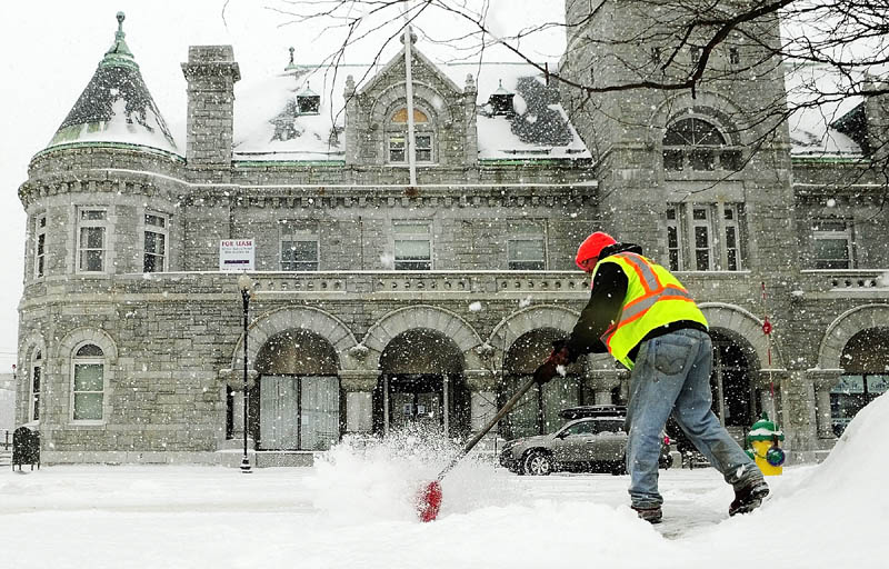 McGee Construction employee Mike Abbott shovels snow this morning on Water Street in front of the Olde Federal Building in Augusta.