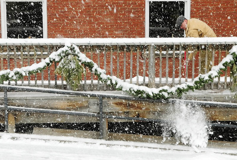 Jason McFarland shovels snow off the deck of Gagliano's restaurant around 11:15 a.m. on Friday, during the winter storm in downtown Augusta.