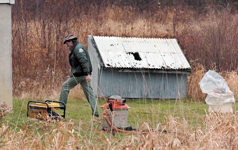 Jon Andrews, an oil and hazardous materials specialist with the Department of Environmental Protection, enters a residence off Drummond Road in Sidney.