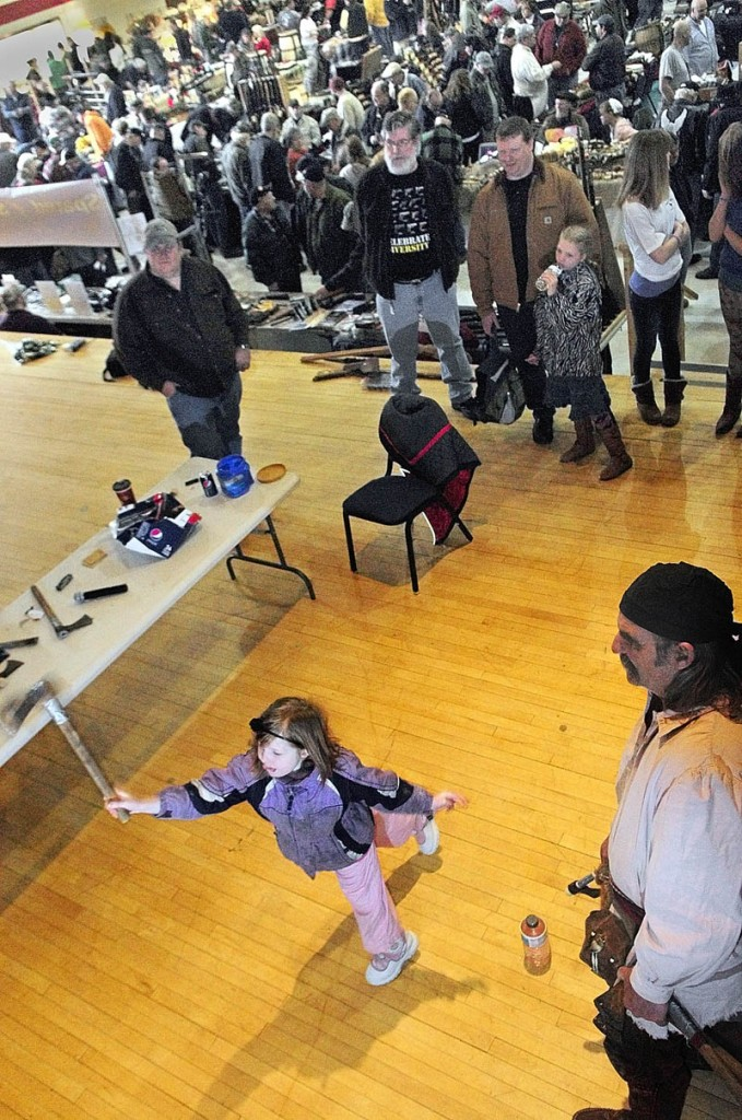 "Molly Turnbull, 7 of Knox, left, tosses a tomahawk at the target, after getting instructions from David ""Gomer"" Bryant, right, during the Ancient Ones of Maine Sport and Gun Show on Saturday at the Augusta Armory. Bryant, of Mount Vernon, said that he's been doing the throwing demonstrations for more than 20 years."