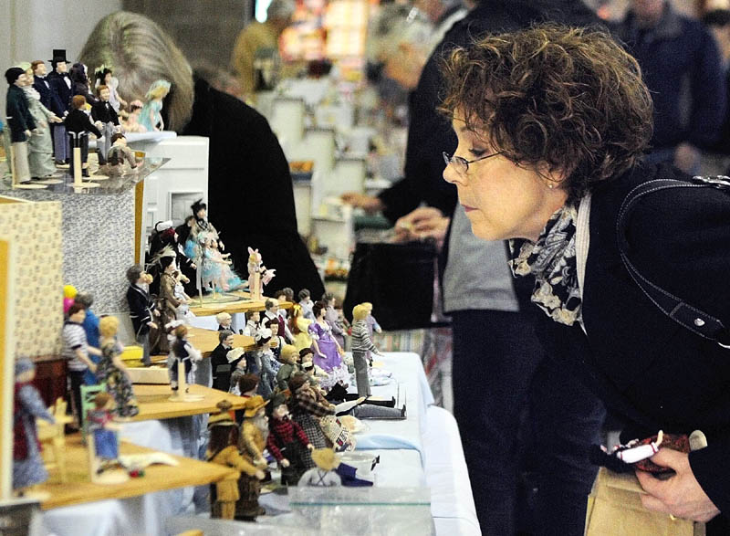 Judy DeGrandpre, of Freeport, looks at porcelain figures made by Elaine Perkins, of Our Dolls in Concord Township, on Saturday, during the Whitefield Lions Club Model Railroad & Doll House Show at the Augusta armory. DeGrandpre said that she had many of figurines made by Perkins.