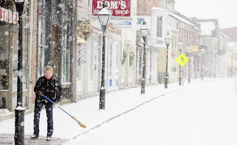 Linda Lesieur sweeps snow off the sidewalk this morning in front of the Earthbound shop on Water Street in downtown Hallowell
