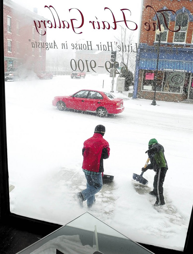 Quincy Tobias, left, 9, and Sam Crilly, 6, shovel snow in front of The Hair Gallery, where both their mothers work, on Water Street in downtown Augusta on Friday, during the winter storm in downtown Augusta.