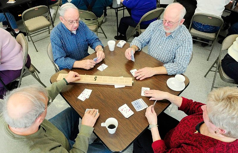 Roland Nault, left, moves a peg while playing cribbage with Lou Turmelle, Peter Bernier and Lorette Beland on Tuesday at the Buker Center in Augusta. There is a weekly cribbage session for seniors there every Tuesday from noon to 3 p.m.