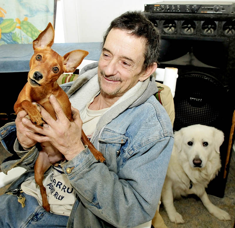 Gary Prentiss holds his dog, Ginger, as Angel sits behind him, at his home in Waterville on Feb. 4. Prentiss said Ginger is recovering after being struck by a car recently.