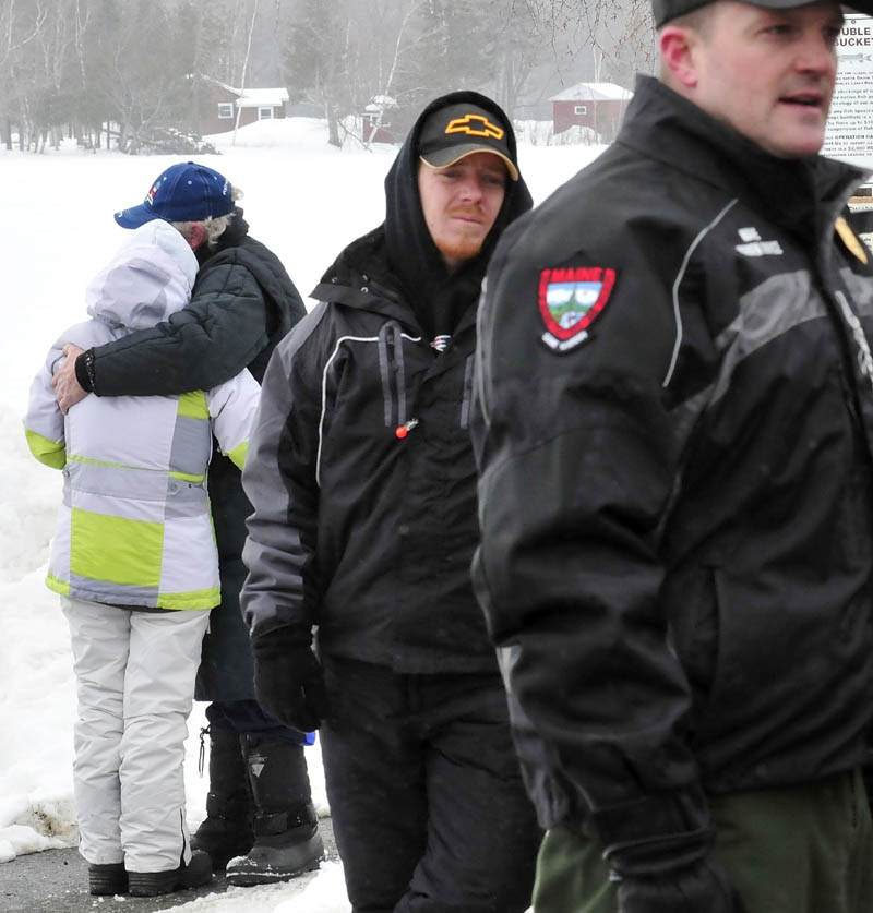 John Spencer Sr. and Jackie Henderson, relatives of two of the missing snowmobilers, hug after becoming emotional as Warden Service Cpl. John MacDonald updates news media on Wednesday about the search for the missing snowmobilers. Spencer is the father of John Spencer Jr. and Henderson is the wife of Glenn Henderson.