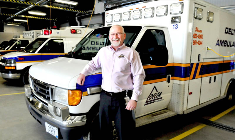 Delta Ambulance Director Tim Beals beside ambulances at the new Waterville headquarters. The company has earned the 2012 Business of the Year award from the Mid-Maine Chamber of Commerce.