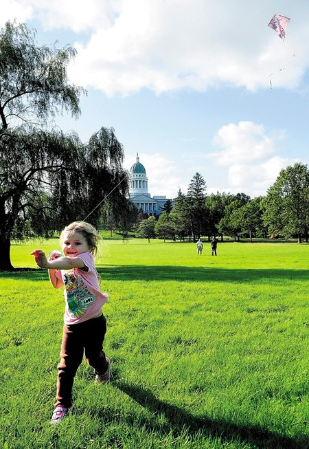 A child runs pulling a kite in October 2011 across Augusta's Capitol Park. Rep. Craig Hickman, D-Winthrop, has sponsored a bill to require that edible landscaping be placed in a portion of Capitol Park.