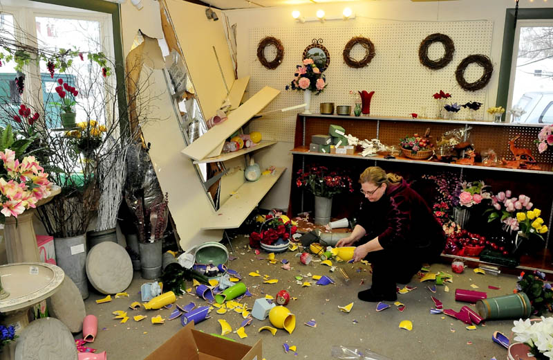 Boynton's Greenhouse Manager Ellen Withee picks up inventory that was knocked down after a truck slammed and punctured a wall at the Skowhegan business on Wednesday evening. Withee said she believes there may be $5,000 worth of damage.