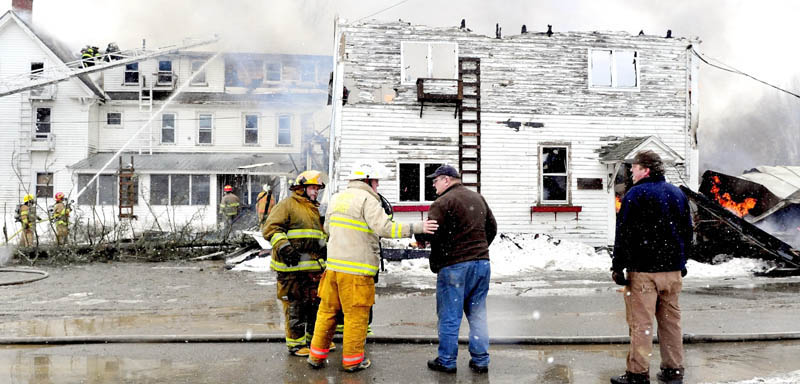Unity Fire Chief Dennis Turner puts a hand on building owner Ralph Nason Sr. as fire consumes his seven-apartment building on Main Street in Unity on Saturday. At right is Ralph Nason Jr., who said the fire may have started near a boiler and the building is insured. There were no reported injuries.