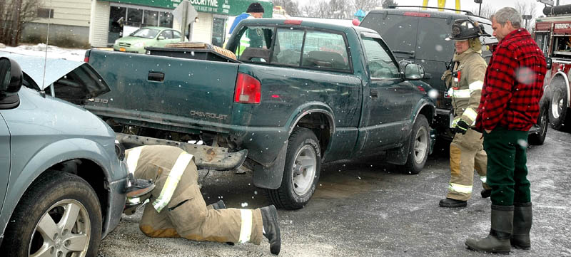 Tom Proctor, 57, of Moscow, in plaid jacket, watches after his green Chevrolet pick-up truck was involved in an accident Friday morning. The truck was totaled in a weather-related accident that involved three vehicles on Madison Avenue in Skowhegan.