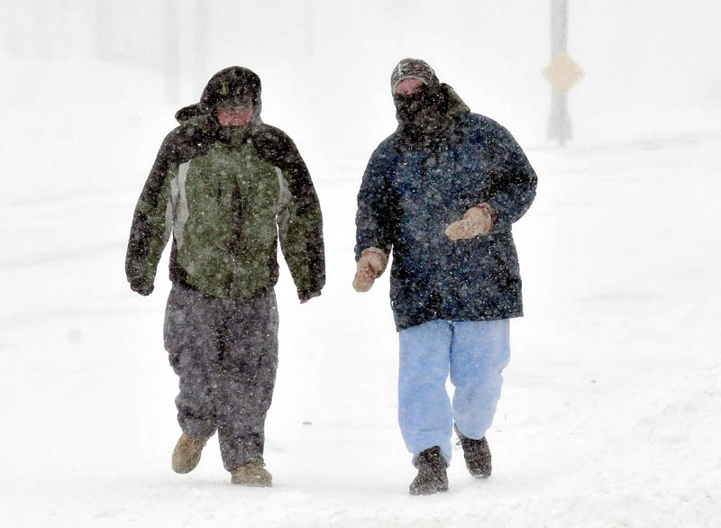 Nick Hunt, left, and Patrick Malloy walk into wind-blown snow in Waterville during blizzard-like conditions on Saturday. Both men said the weather was both cold and terrible.