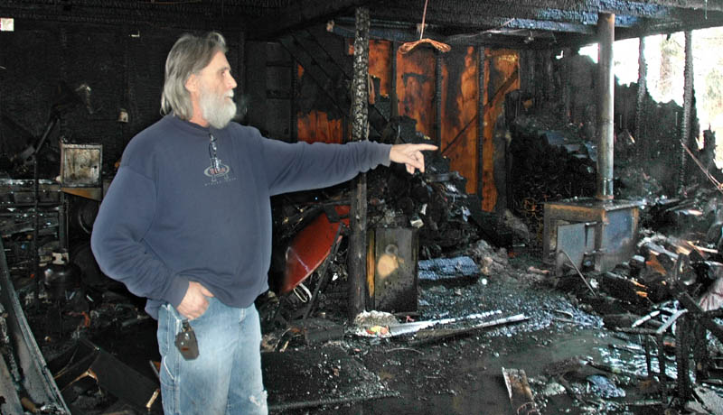Ron Pelletier, of St. Albans, points to the shell of a Harley Davidson motorcycle destroyed in a garage fire Wednesday morning at his home on Webb Ridge Road. Pelletier said he lost $100,000 in tools and equipment.