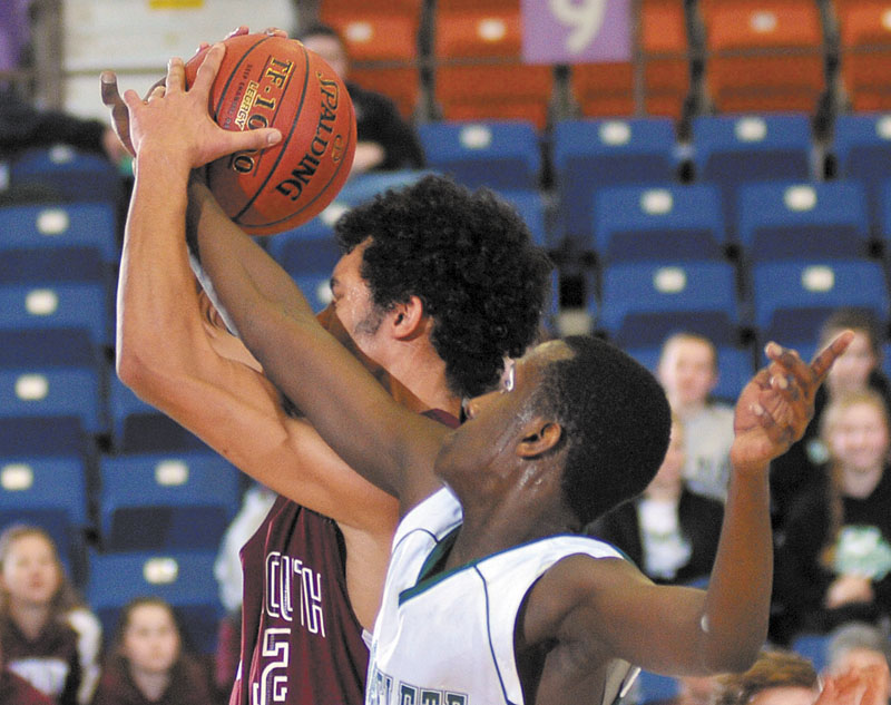 Monmouth Academy's Marcques Houston get his shot blocked by Serge Nyirikamba of Waynflete during a Western Class C quarterfinal Monday in Augusta. Waynflete won, 78-47.