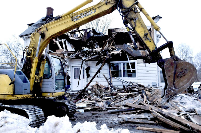 "Nick Ferreira uses an excavator to clear debris in front of 178 Main Street in Unity on Tuesday. The work was done so former tenants could enter the burned building to retrieve belongings. Owner Ralph Nason Sr. said he has not decided what to do with the lot. ""Right now I'm waiting on the insurance company,"" Nason said."
