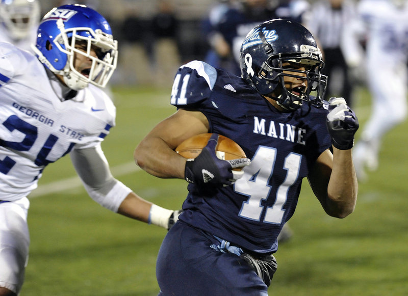 Maine running back Nigel Jones breaks away from Georgia State's Kail Singleton on the way to a 9-yard touchdown run in a game last year. The University of Maine will will be on the road for four of its first five football games this fall, according to the schedule released by the college Thursday afternoon.