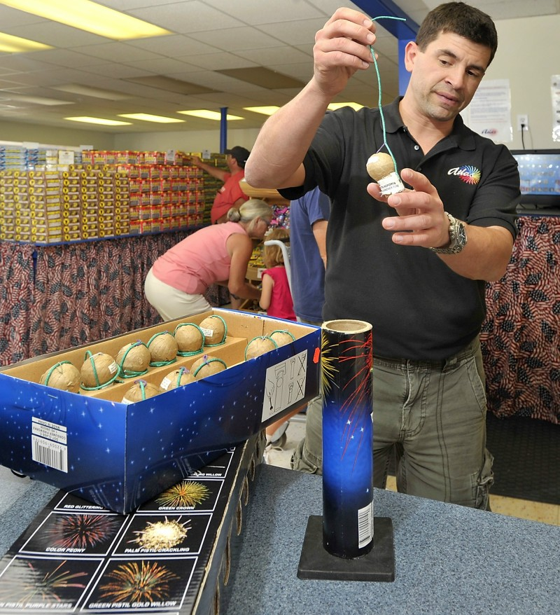 In this June 2012 file photo, store manager Scott Mitchell explains how the newer fireworks are safer than the older models at Atlas Fireworks Company on Route One in Scarborough. Bills repealing and restricting Maine's fireworks laws are currently in front of the Legislature.